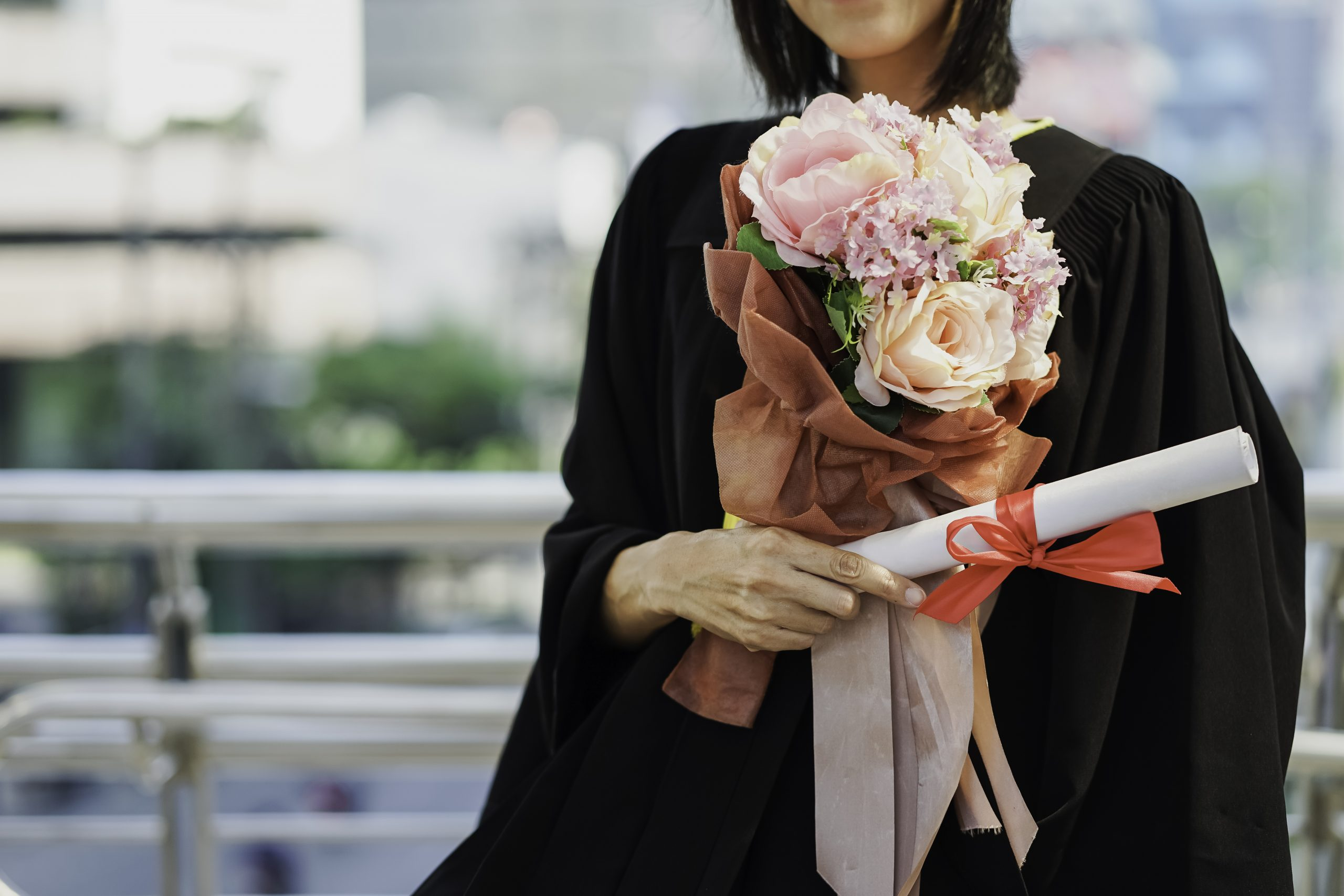 college graduate holding bouquet of flowers