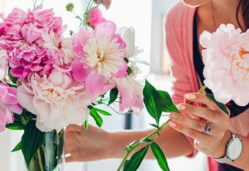 young woman in pink cardigan assembling a pink bouquet in a glass vase