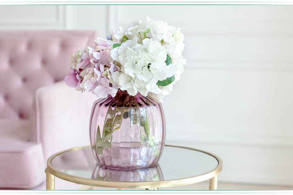 white and pink hydrangea in vase on glass table