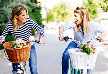 two young women on their bikes laughing together