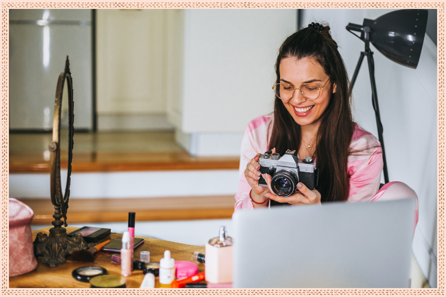 woman smiling at camera in front of vanity with laptop on