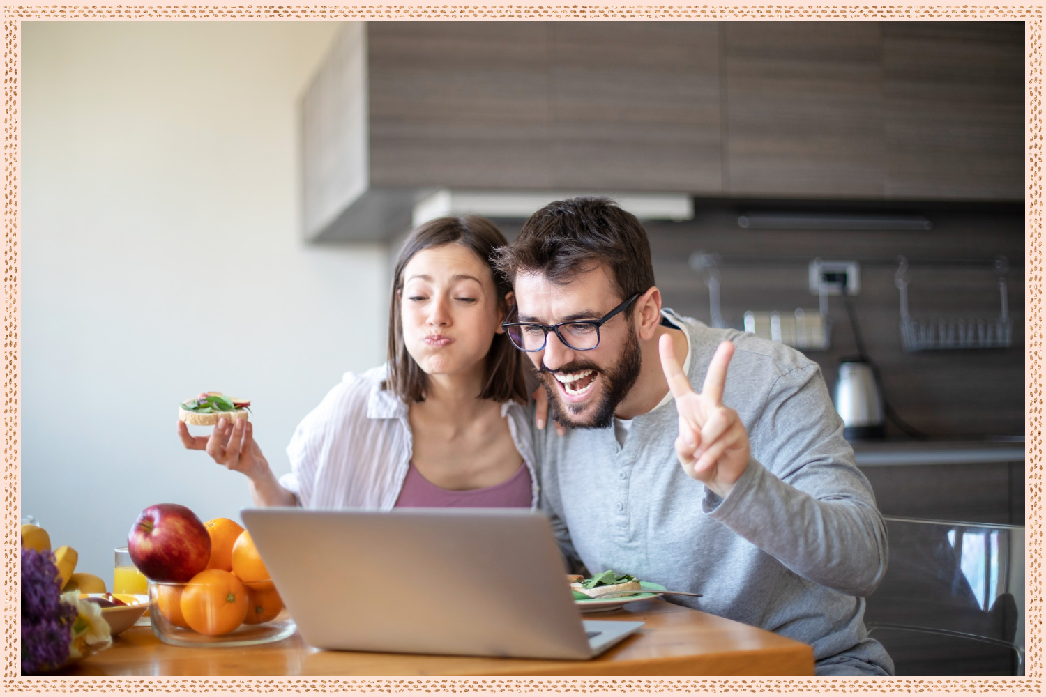 couple eating breakfast while video chatting with someone on their laptop