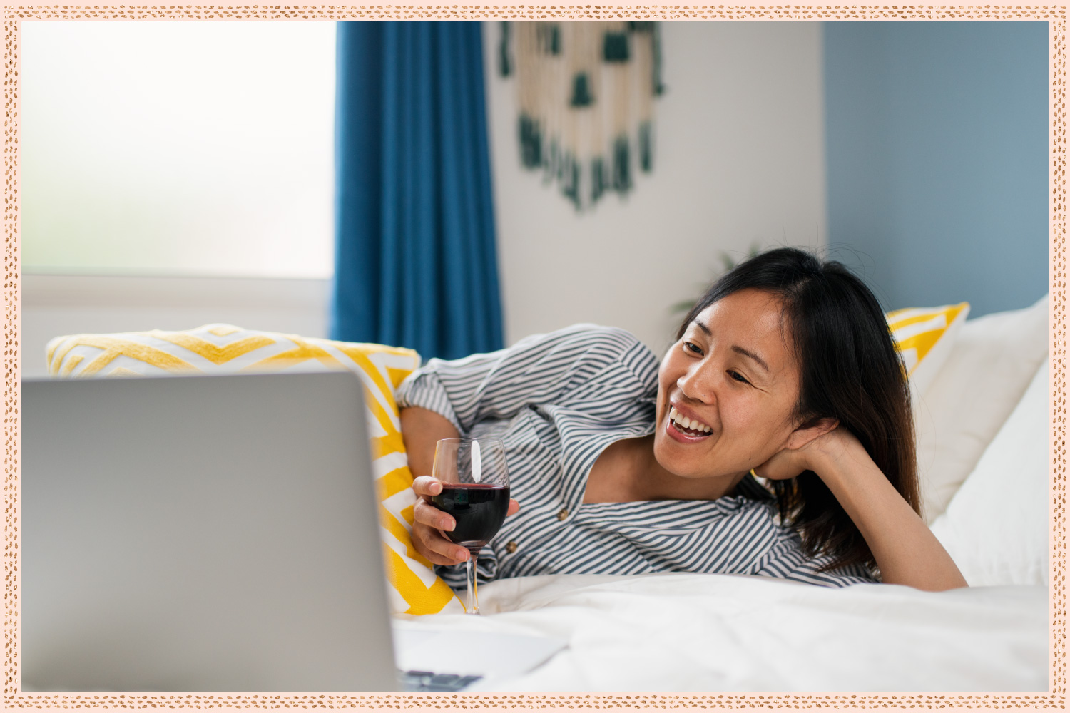women in bed with a glass of red wine smiling at the laptop in front of her