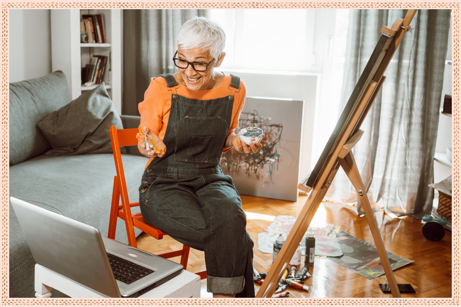 older woman painting a canvas on an easel while videochatting someone with laptop