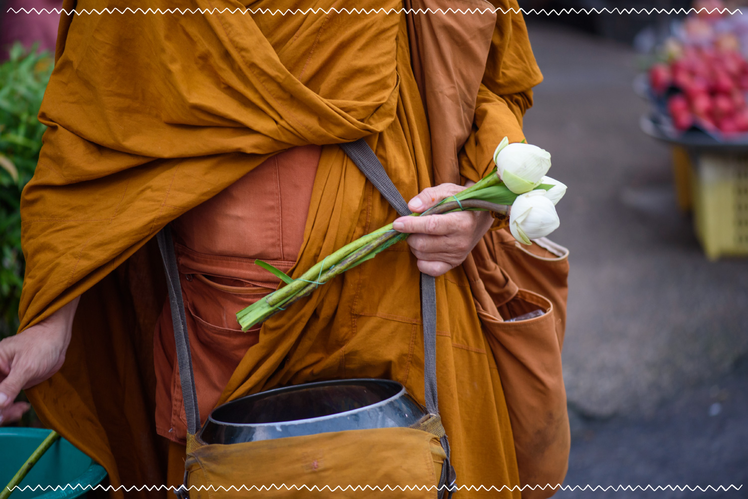 man in monk clothing holding white flowers