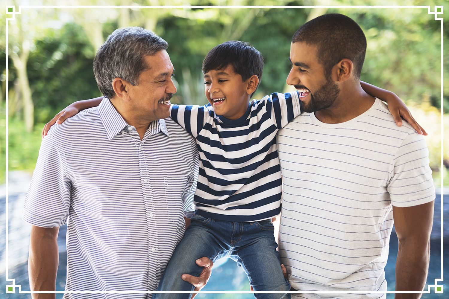 father and grandfather holding young boy, laughing