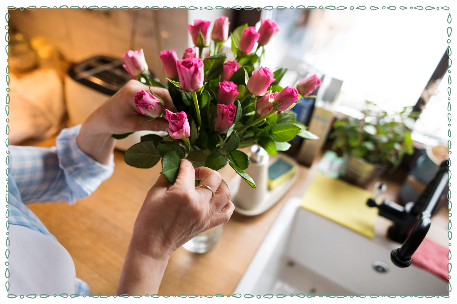 hands arranging roses in a vase on a kitchen counter