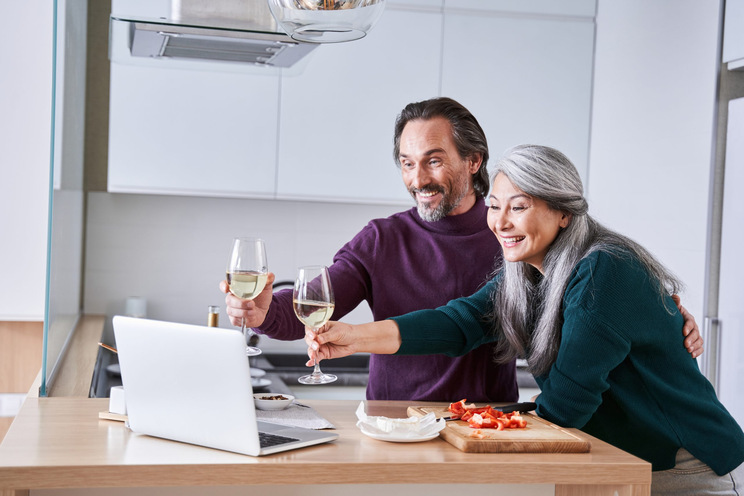 Friends celebrating with drinks with online chat on laptop