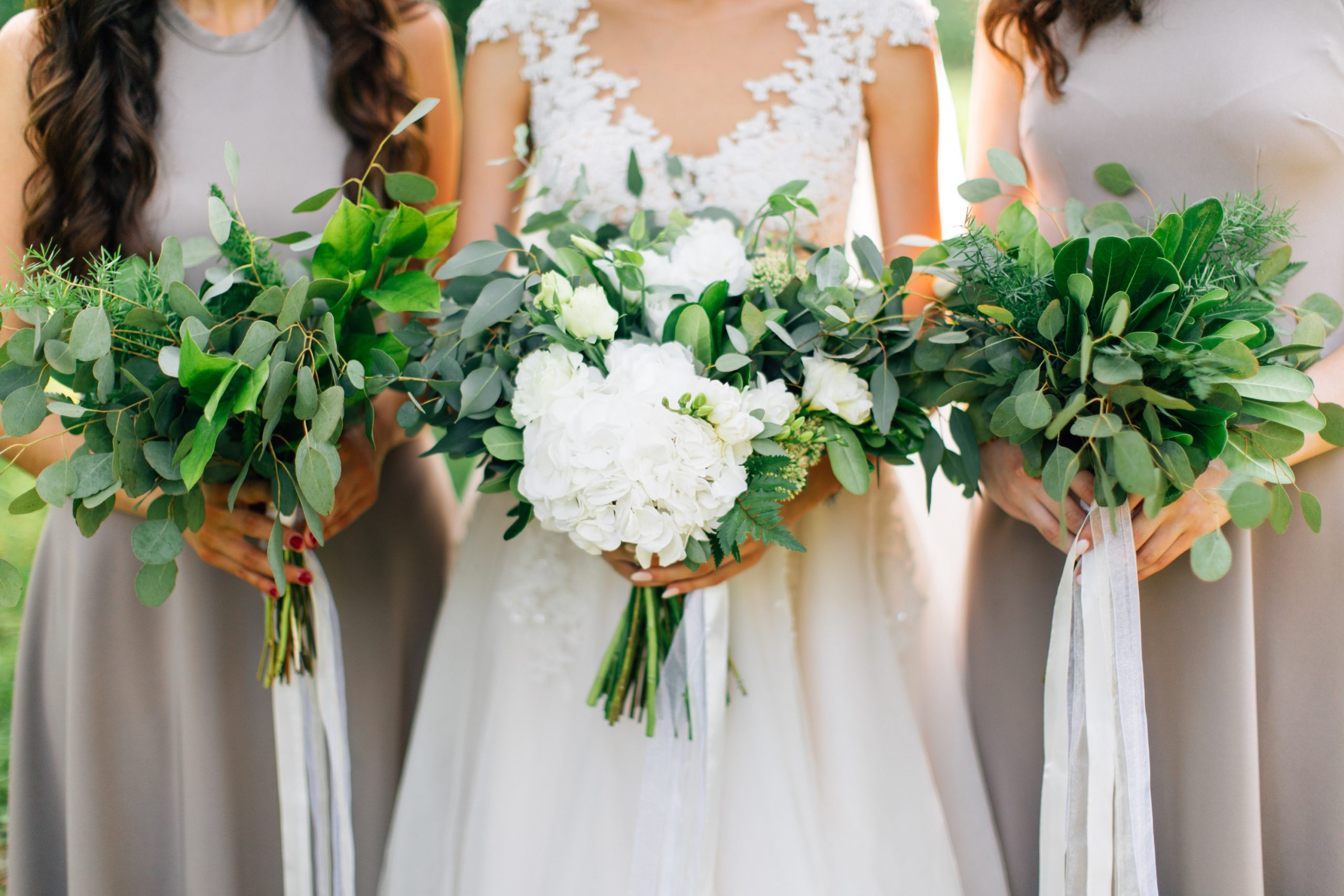 Bridesmaids holding white flower bouquets